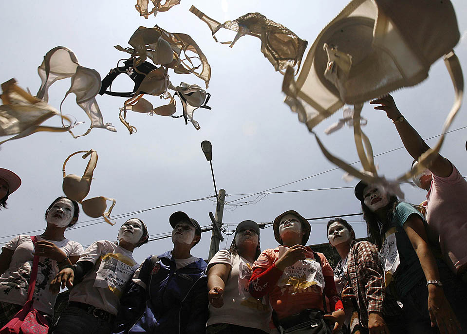 Dismissed workers of Triumph International Philippines throw bras in the air during a demonstration in front of the Department of Labour and Employment in Manila