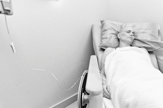 Jen sleeps while receiving chemotherapy treatment. On top of the physical toll taken by chemotherapy, the daily emotional struggle is exhausting.