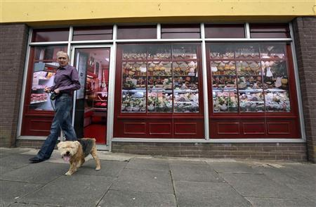 Kevin Maguire walks his dog past a vacant shop, with graphics pasted to the outside to make it look like working butchers shop, in the village of Belcoo, Northern Ireland