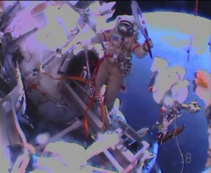 Russian astronaut Oleg Kotov holds an Olympic torch as he begins a spacewalk outside the International Space Station