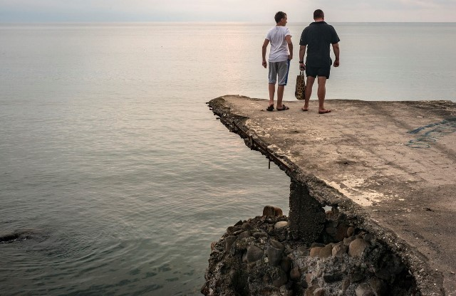 Two men are looking at the Black Sea, sitting on a concrete platform. Sukhumi