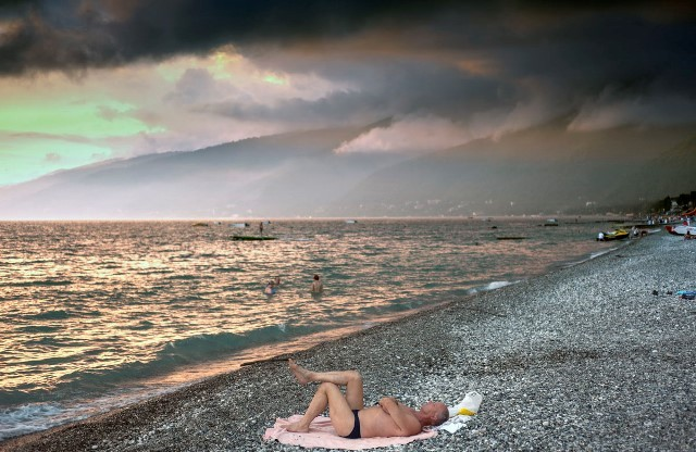 A man in swimming trunks lies on the beach in Gagra, the busiest resort in Abkhazia, very close to Sochi Olympic site and Russian border.