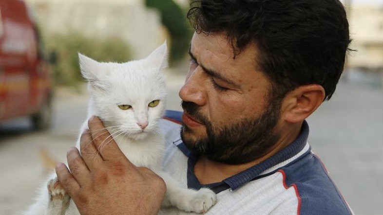 Alaa, an ambulance driver, carries a cat in Masaken Hanano in Aleppo