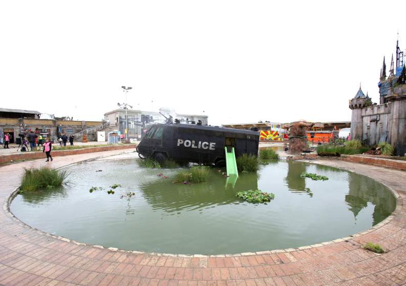 Image #: 38872741    An amour plated police riot van built to serve on the streets of Northern Ireland in a lake, during the press day for the artist Banksy's biggest show to date, entitled 'Dismaland', at Tropicana in Western-super-Mare, Somerset.       PA PHOTOS /LANDOV