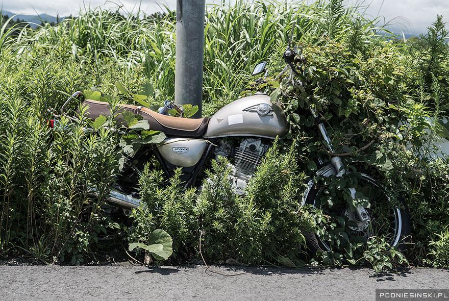 O motocicletă legată de un stâlp e absorbită încet de câmpul din jur