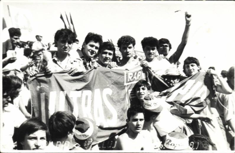 """București, 1988:  Regimul comunist susținea că reprezintă poporul și utiliza stadionul pentru a organiza spectacole gigantice de auto-glorificare. Românii erau obligați să participe la """"zilele de sărbătoare"""", fluturând steaguri roșii cu secera și ciocanul sau coregrafii din cartoane ținute deasupra capului. Atent supravegheate, zeci de mii de persoane formau mesajele 'Trăiască Partidul Comunist Român', 'Ceaușescu, România, PCR' sau 'Epoca de Aur', în timp ce liderii comuniști se bucurau frenetic pe podium, de susținerea pe care stadionul părea să le-o acorde. Același stadion de fotbal, dar în zi de meci, aduce o altă atmosferă. Este tot zi de sărbătoare, doar că e bucuria luptei cu adversarul, nu a aplauzelor regizate. În timp ce însemnele regimului se găsesc doar în zona oficială, culorile echipei favorite sunt omniprezente pe eșarfe, mesaje și steaguri, alături de simboluri rebele ale mișcării ultras din Occidentul liber: capete de mort, tigri, lei. Spectatorii contestă deciziile arbitrului și îl bănuiesc că trage pentru ceilalți, pe care îi consideră """"echipa sistemului"""". Cu motiv sau fără, nemulțumirea crește, iar scandările ironice sunt înlocuite de înjurături.  În curând, nu mai este clar dacă huiduielile sunt la adresa deciziilor din teren, a rivalilor sau direct contra autorităților. Intervin milițienii pentru a ține în frâu tribuna, lovesc în stânga și-n dreapta, primesc ripostă. Nu este ușor să reduci la tăcere 10.000 de rebeli ai momentului... într-un final, echipa pierde și retrogradează, publicul se resemnează și dă vina pe corupția sistemului. Pe 21 Decembrie 1989, galeria Rapidului se adună în grup organizat, ca de obicei, însă nu are programat un derbi. Suporterii vin în Piața Universității pentru o altă confruntare, ce se va dovedi pe viață și pe moarte: contra dictaturii comuniste. Nu au cu ei steagul din fotografie, dar glasurile și revolta sunt prezente ca de obicei. Se poate lesne bănui că au participat și sustinători ai celorlalte echipe bucureș"""