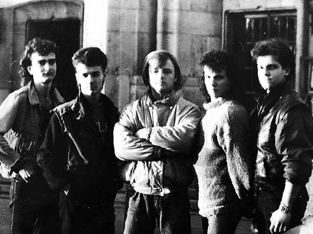 """București, 1989, anteRevoluție: A fi rocker sau punker era o misiune dificilă în timpul regimului comunist: muzica occidentală """"decadentă"""" era interzisă, pletele sau crestele erau vânate pe stradă de către milițieni, a avea o geacă de blugi era mai mult o dorință decât o realitate, în condițiile unei penurii generale.  În plus, este un pic mai greu să cânți la o chitară electrică când se taie curentul. în ciuda restricțiilor, numeroase grupuri de tineri încercau sa se exprime liber, deși trăiau într-o dictatură.  Când a venit vremea revoltei, ei au fost în primele rânduri. Al patrulea de la stânga la dreapta este Mihai Gâtlan, prima victimă a represiunii de pe 21 Decembrie 1989. Prietenii îi spuneau Micky Rockerul."""